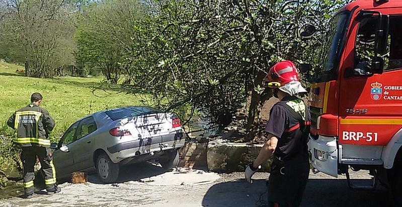Los bomberos liberan a un hombre atrapado entre su vehículo y una roca del cauce de un riachuelo