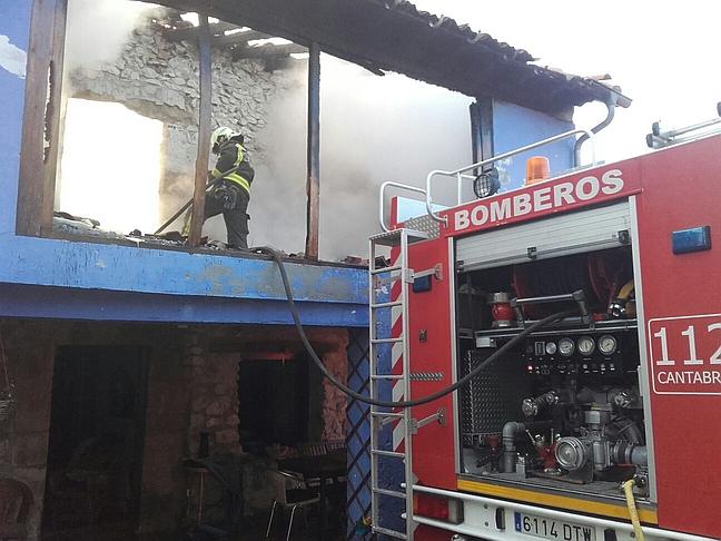 Bomberos del 112 trabajan en la extinción de un incendio en una vivienda en Udías